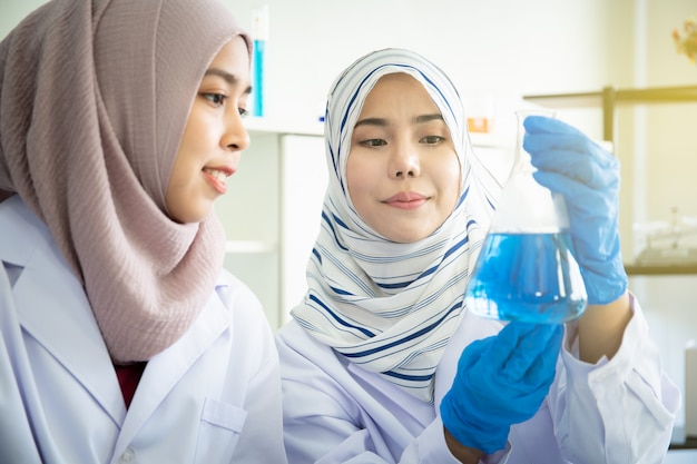 Two muslim chemical scientists doing the experiment in laboratory