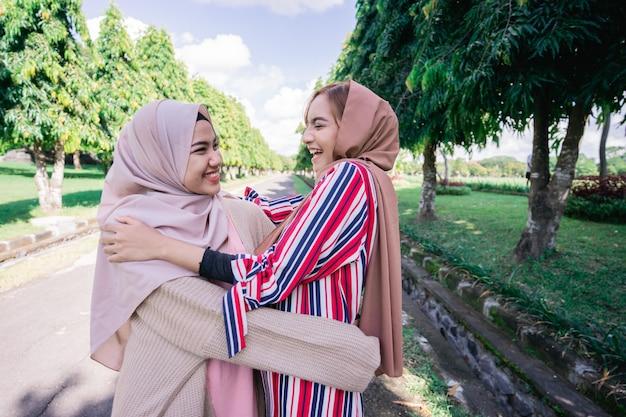 Two muslim girls hug on the sidewalk. feel joyfull and happy together.