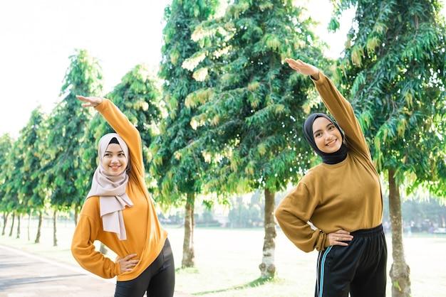 スカーフを着た2人のイスラム教徒の少女が、公園の部屋の外で運動するために手を上げて筋肉を伸ばします。