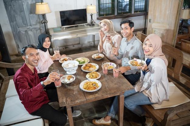 ヒジャーブを身に着けている2人のイスラム教徒の男性と3人の女性は彼らの食べ物を喜んで持ってきます