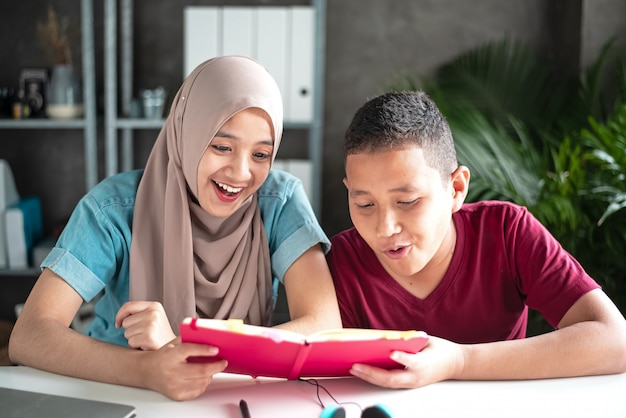 Two muslim students reading book together