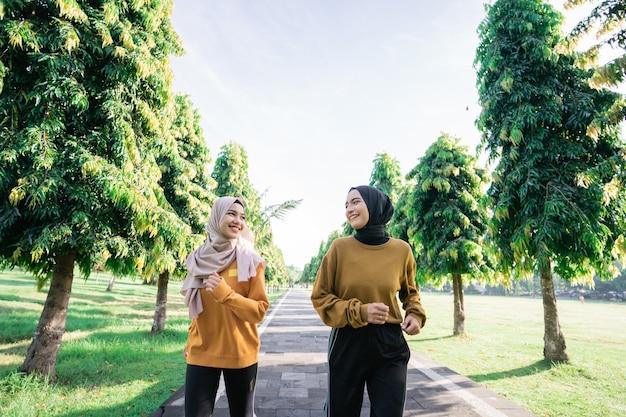 公園で断食をする直前に一緒に屋外スポーツをしているベールの2人のイスラム教徒の10代の少女