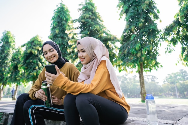 Two muslim teenage girls using a smartphone and holding drinking water bottles after doing sports together in the afternoon in the park