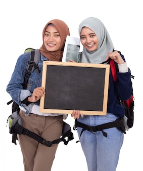 Two muslim woman backpacker with blackboard