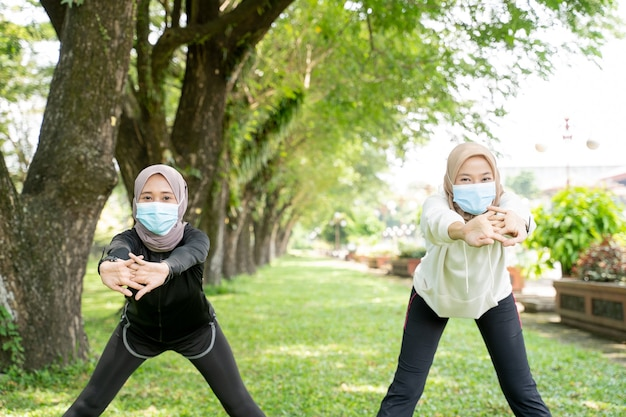 Две подруги-мусульманки тренируются вместе и носят маску