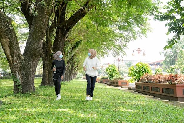 Две подруги-мусульманки вместе бегают трусцой в маске