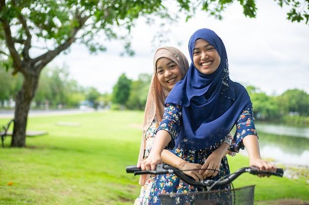 2人のイスラム教徒の女性が庭で自転車に乗る