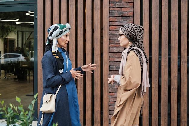 전통 의상을 입은 두 명의 이슬람 여성이 도시 중심부에서 만나면서 서로 이야기를 나누고 있습니다.