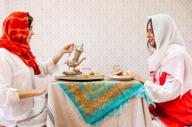 Две мусульманские женщины, сидящие за столом