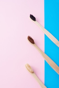 Two natural wooden toothbrushes on a blue and pink color background