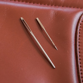 Two needles on brown leather with handmade stitches