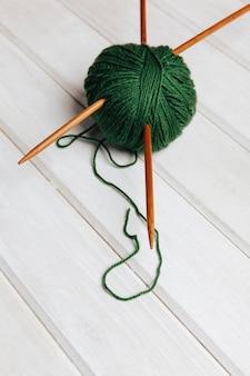 Две иглы в шаре из зеленой шерсти