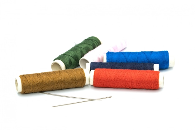 Two needles and six colorful core threads on white background