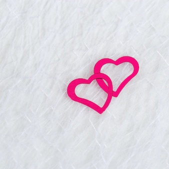 Two neon pink hearts on a white blurred translucent fabric. greeting card, background or invitation with copy space for text. flat lay.