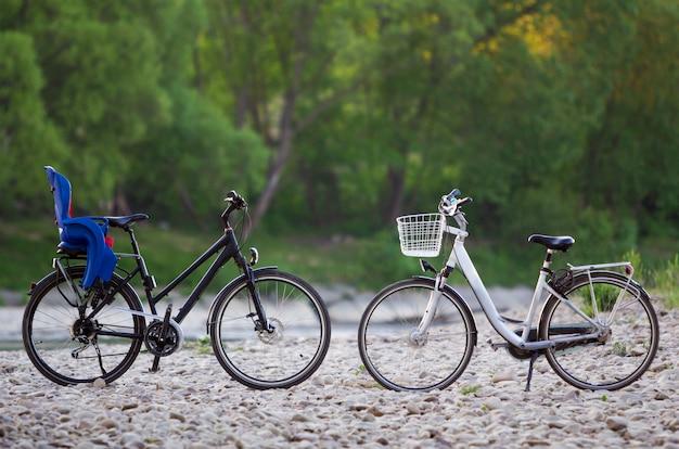 青いプラスチックのチャイルドシートと黒とぼやけた緑の木々の夏に太陽の小石に照らされて立っているバスケットと白の2つの新しい近代的な自転車。観光と家族旅行のコンセプト。