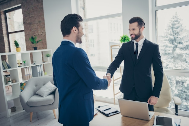 Two nice attractive stylish elegant classy chic cheerful men economist lawyer banker financier marketer shaking hands meeting appointment in light office workplace workstation