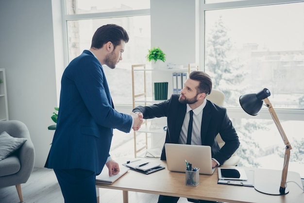 Two nice attractive stylish elegant workpeople guys economist lawyer banker agent broker sales representative shaking hands meeting in light office workplace workstation