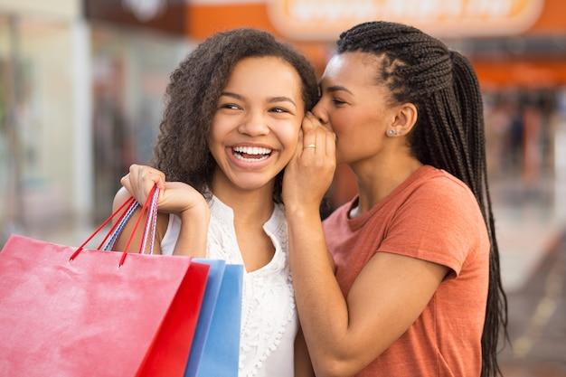 쇼핑하고 비밀을 공유하는 두 명의 멋진 흑인 소녀