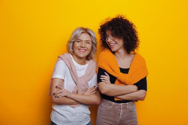 巻き毛の2人の素敵な白人女性は、笑顔で楽しんでいる間、黄色の背景に交差した手で自信を持ってポーズをとっています