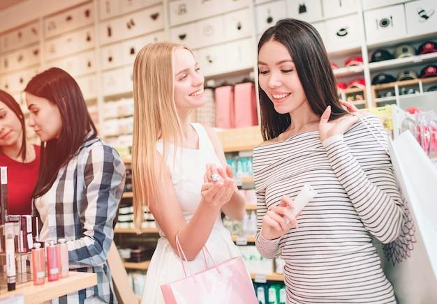 앞에 두 명의 멋진 소녀가 서서 웃고 있습니다. 아시아 소녀는 눈먼 소녀가 손에 들고 있는 화장품을 보고 있습니다. 금발 소녀는 아시아 소녀를 찾고 웃고