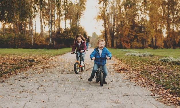 자전거를 타는 두 명의 멋진 아이들이 해가 질 때 공원에서 즐겁게 놀고 있습니다.