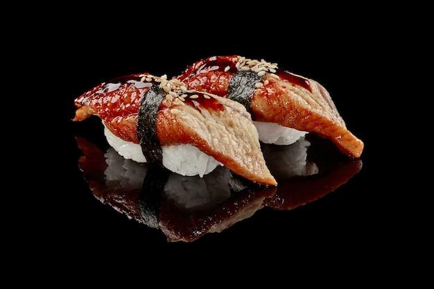 Два суши нигири с соусом унаги из угря и кунжутом
