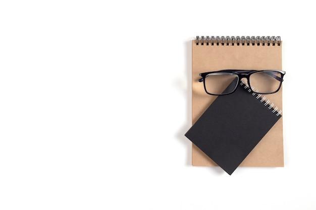 На белой поверхности лежат два блокнота и стакана. блокнот из переработанной бумаги как концепция экологии, пригоден для вторичной переработки, без отходов. офис, бизнес, образование. выборочный фокус. скопируйте пространство.