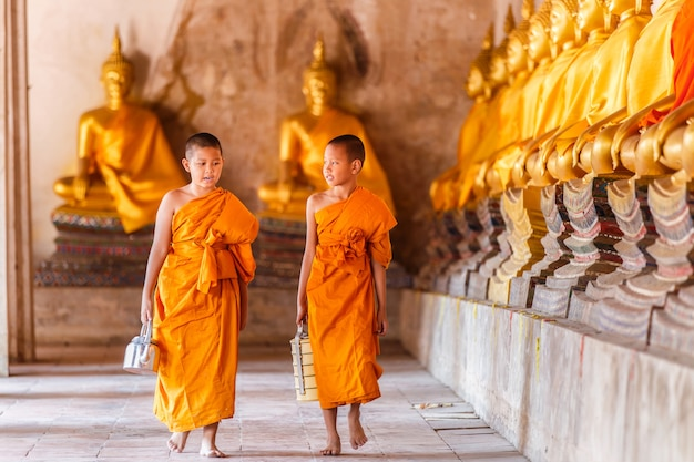 Two novices walking and talking in old temple at ayutthaya province, thailand