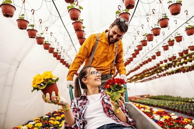 楽しい2つの保育園の庭の労働者。女性がそれに座っていると花が付いている鍋を保持しながら手押し車を押す男。周りは色とりどりの花でいっぱいです。