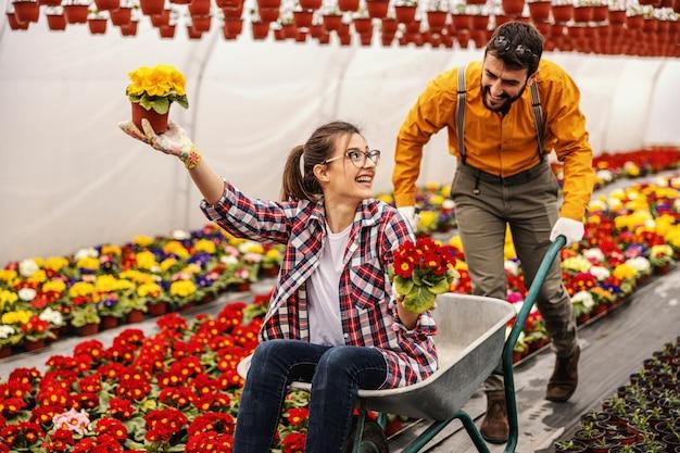 楽しい2つの保育園の庭の労働者。女性がそれに座っていると花が付いている鍋を保持しながら手押し車を押す男。
