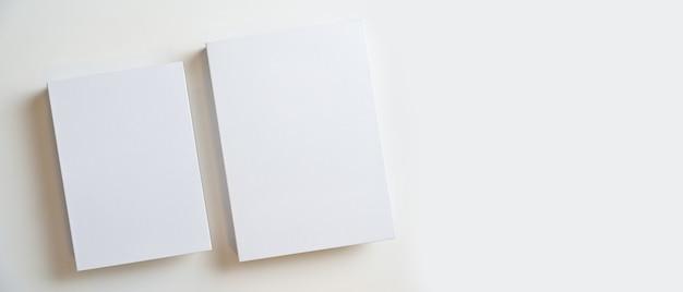 2冊の白紙の本は白い背景の上にあなたのテキストやブランドを表示するための空きスペースで覆われています
