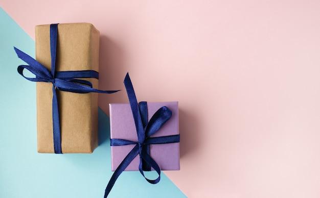 Две красочные подарочные коробки с голубой лентой и бантом на сине-розовом фоне с копией пространства