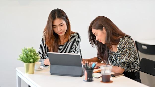 Две женщины изучают онлайн-класс и вместе читают лекцию в коворкинг-космическом планшете