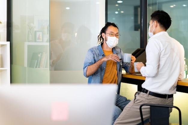 사회적 거리 연습 사무실과 함께 새로운 정상에서 커피를 마시면서 이야기하는 두 명의 직장인. 그들은 안면 마스크를 착용하여 새로운 정상적인 생활 방식으로 covid-19 코로나 바이러스 감염 위험을 줄입니다.