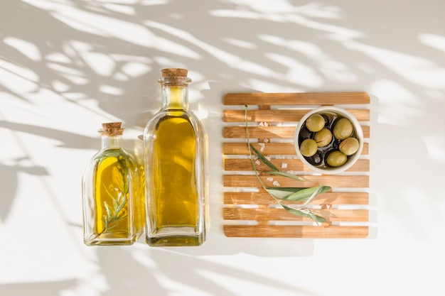 Two oil bottles with olives on stripped wooden board