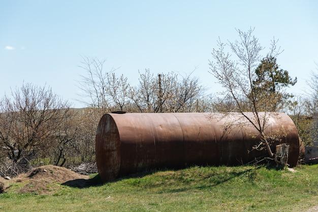 두 개의 오래 된 버려진 녹슨 배럴은 잔디에 야외에 누워