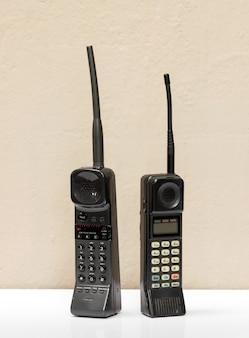 通信の概念で並んで立っているアンテナと数字キーパッドを備えた2つの古い黒のヴィンテージ携帯電話
