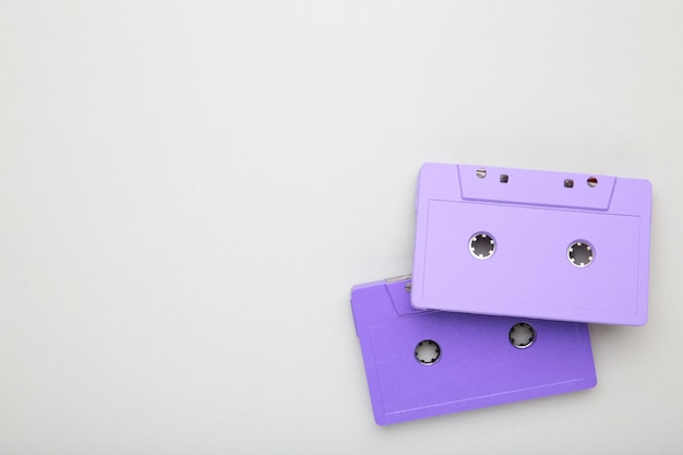 Two old colorful cassettes on a grey background. music day