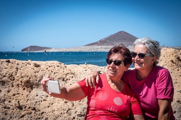 Два старых друга, сидящие на скамейке, смотрят на свой мобильный телефон и делают селфи. концепция связи и дружбы. за ними гора и море. рай для любителей серфинга