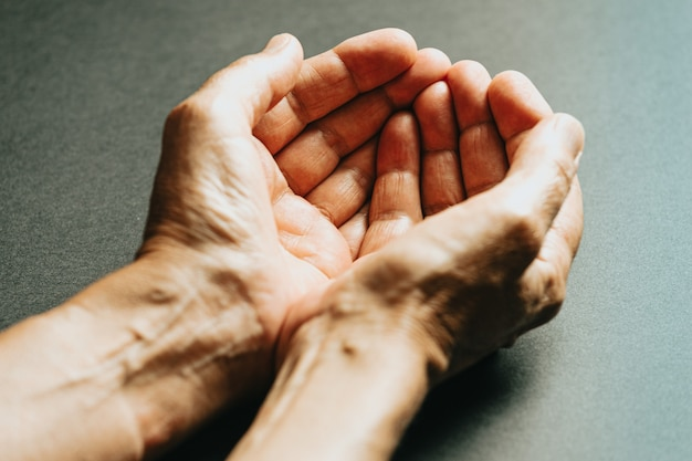 Two old hands waiting for something to fall into them