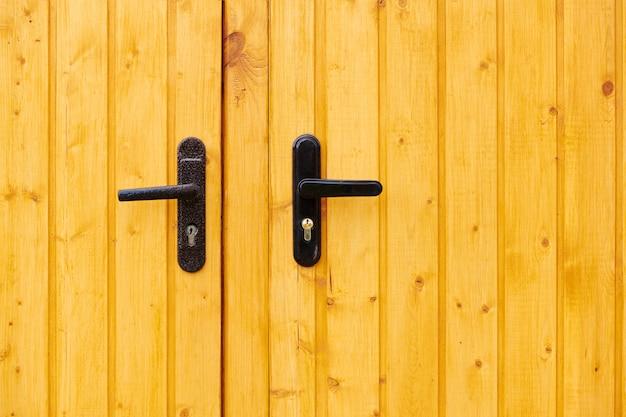 木製のドアにロックが付いた2つの古い金属製のドアハンドル。クローズアップビュー