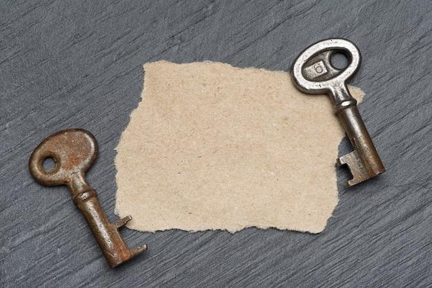 2つの古いさびた鍵と黒いスレートの表面に茶色の紙片