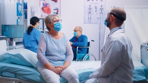 Два пожилых пожилых человека у врача в масках и разговаривают с медсестрой и врачом в защитной одежде. современная частная клиника или больничная палата во время пандемии covid 19. запись на прием к врачу