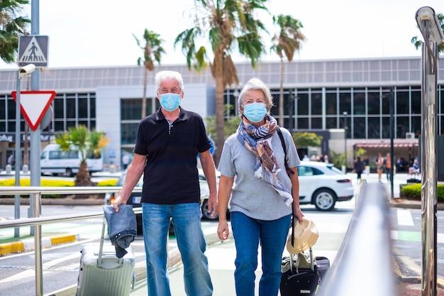 코비드-19 또는 새로운 유형의 독감 또는 바이러스를 방지하기 위해 의료 및 수술용 마스크를 착용한 검역 및 폐쇄 후 함께 여행하는 두 노인 - 여행 가방을 든 성숙한 사람들
