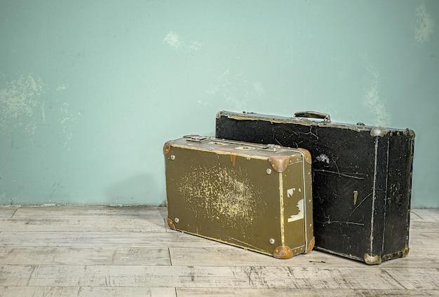 空の部屋のぼろぼろの壁の近くにある2つの古いスーツケース。コピースペースのあるレトロなスタイルのラゲッジコンセプト。