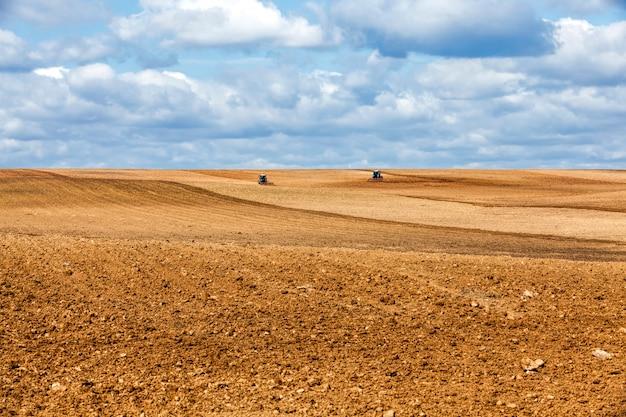 파종을 위해 필드를 준비하는 동안 필드에서 토양을 경작하는 두 개의 오래된 트랙터, 흐린 시간에 풍경