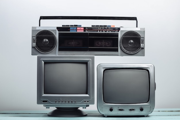 Two old tv receiver with audio tape recorder on a white wall. retro media