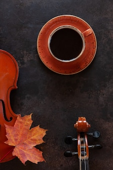 Two old violins, a cup of coffee and autumn maple leaf