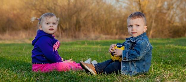 2歳の男の子と女の子が春にガラスの上にプレーします。