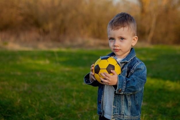 Двухлетний мальчик держит футбольный мяч в парке.